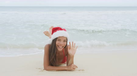 hat : Christmas beach woman wearing santa hat and bikini waving hand saying hello hi looking at camera on holidays travel vacation getaway travel relaxing on beach. Beautiful young female model.