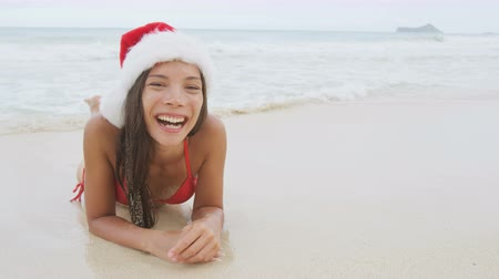 lefekvés : Christmas beach vacation travel woman wearing Santa hat and bikini laughing having fun on winter holidays getaway on tropical beach. Multicultural Asian Chinese  Caucasian model happy sitting in sand