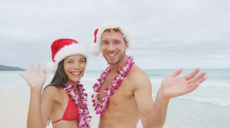 hat : Christmas beach Hawaii couple waving hands saying hello and hi looking at camera.  Hawaiian beach people wearing santa hat and Lei happy on Christmas winter holidays. Shot on RED EPIC in SLOW MOTION.
