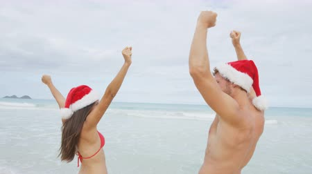 utazó : Christmas beach travel vacation couple in Santa hat jumping of joy cheering on tropical Caribbean winter holidays getaway. Beautiful couple in bikini having fun under the sun traveling.