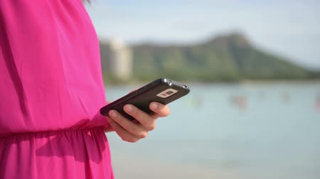 usuário : Close up of Woman Wearing Fuchsia Dress Holding Mobile Phone at the Beach. Girl Using Smartphone App on Smart phone Outside. Stock Footage