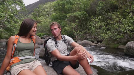 kaland : Young Couple Resting on Boulder at the River Enjoying Adventure Time. Couple Resting After Hiking. Stock mozgókép
