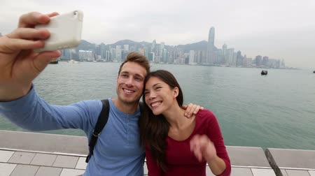vyhlídkové : Selfie tourists couple taking self-portrait picture photos in Hong Kong enjoying sightseeing on Tsim Sha Tsui Promenade and Avenue of Stars in Victoria Harbour, Kowloon, Hong Kong. Travel concept.