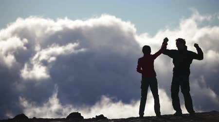 bajnok : Achievement, Success and accomplishment high five concept with hiking people cheering and celebrating of joy with arms raised outstretched up above the clouds on trekking hike. Woman and man Hikers. Stock mozgókép
