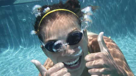 swimming underwater : Woman swimming underwater in pool smiling happy giving thumbs up sign hand waving hands saying hello looking at camera. Young female swimmer with swim goggles at holiday resort.