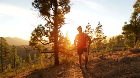 kimerül : Running runner man athlete resting taking break standing relaxing after exercising on mountain forest trail at sunset in amazing landscape nature. Fit handsome athletic male working out outside.
