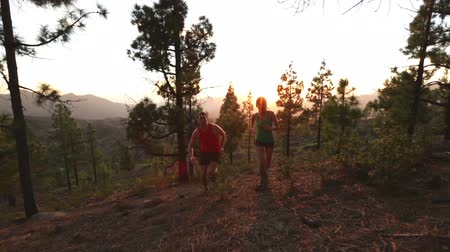 estilo de vida saudável : Running Health and fitness. Runners on run training during fitness workout outside in mountain forest at sunset. People jogging together living healthy active lifestyle outside. Woman and man. 2 clips
