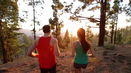 kimerül : Running Health and fitness. Runners on run training during fitness workout outside in mountain forest at sunset. People jogging together living healthy active lifestyle outside. Woman and man. 2 clips