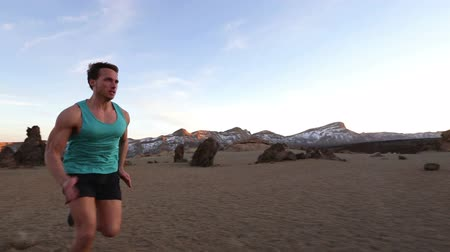 rotaları : Running man sprinting fast. Male runner sprinter at high speed during high intensity interval training workout outdoors in amazing desert mountain nature landscape. Healthy active lifestyle people. Stok Video