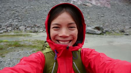 поход : Active outdoors hiker taking selfie using app on smartphone. Happy hiker with mobile phone outside in nature in rain. Girl on hike in mountains. Стоковые видеозаписи