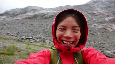 вокруг : People having fun. Active outdoors hiker taking selfie using app on smartphone. Happy hiking girl with mobile phone outside in nature in rain. Girl on hike in mountains.