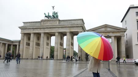 gates : Brandenburg Gate Berlin Germany people. Woman at Brandenburg Gate or Brandenburger Tor standing with umbrealla in rain in Berlin, Germany during travel in Europe.