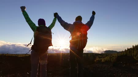 поход : Success, achievement and accomplishment concept with hiking people cheering and celebrating of joy with arms raised outstretched up on trekking hike outside. Hikers having fun at sunset.