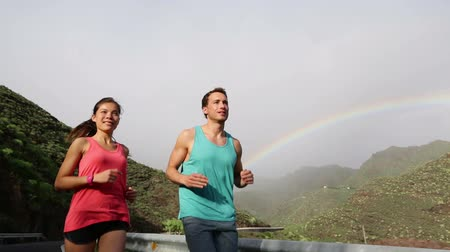 благополучия : Video of male and female joggers against mountains. Young couple are jogging with rainbow in background. Fit man and woman are in sports clothing. Стоковые видеозаписи