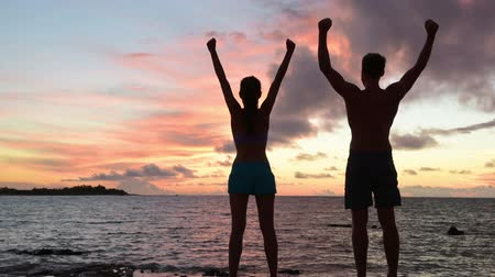 celebrating : Rear view of young couple with arms raised by sea. They are in swimwear cheering at beach during sunset. They are representing concepts of success and accomplishment.
