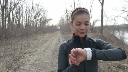 oran : Runner using smartwatch fitness tracker and heart rate monitor watch jogging on trail in forest. Female athlete checking her cardio traning data during workout outside in running park. Stok Video