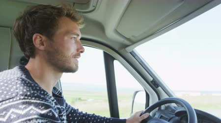 inside bus : Young man driving mobile home car. Side view portrait of smiling male on roadtrip. Handsome man is concentrating while driving automobile motorhome.