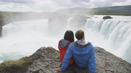 hiking : Couple watching majestic waterfall Godafoss. Multiethnic man and woman visiting famous tourist attraction of Iceland. Male and female are enjoying their vacation relaxing after hiking