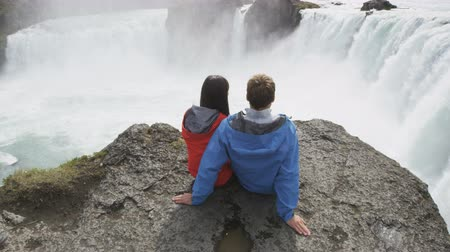 aşağı bakıyor : Young couple watching Godafoss waterfall from cliff. Man and woman are relaxing on rock during vacation. Male and female are enjoying majestic view of famous attraction in Iceland. Stok Video