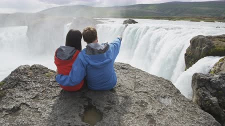 vacation : Man talking to woman while showing majestic waterfall Godafoss from cliff. Tourist couple enjoying idyllic view famous attraction in Iceland. Male and female are on their vacation travel.