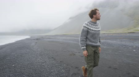 pulóver : Young man walking on black sand beach by mountain wearing Icelandic sweater on Iceland. Male is in warm clothing during vacation. Man is on walking sea shore.