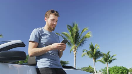 başarılı : Man using smartphone leaning on convertible car. Low angle view of young successful male professional texting using mobile cell smart phone against clear blue sky. Man driver getting in car driving.