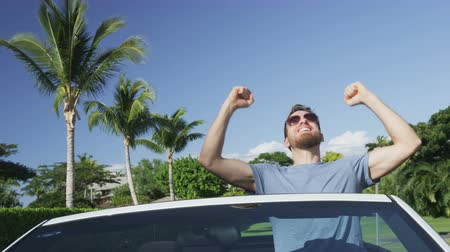 tonları : Enthusiastic young happy man cheering while sitting in convertible car. Male driver is clenching fists while celebrating success in car. Handsome man driving wearing sunglasses against blue sky. Stok Video