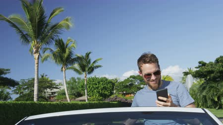 řidič : Happy young man taking smartphone selfie while sitting in convertible car. Handsome male model is smiling while photographing himself using mobile cell smart phone. Shot on RED EPIC.