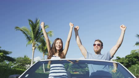 kutluyor : Excited young couple cheering while sitting in convertible. Male and female are clenching fists while celebrating success in car. Man and woman are enjoying against blue sky during summer.