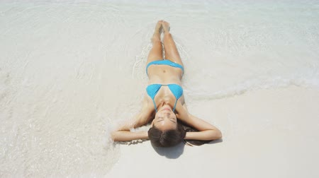 sensuous : Beach happy woman sunbathing lying in sand smiling . High angle view of waves reaching relaxed woman in blue bikini lying on beach. Beautiful girl is on summer vacation