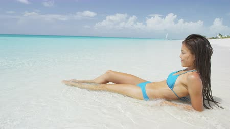 sensuous : Beautiful young woman sunbathing on sea shore. Attractive female in blue bikini is looking at tranquil view of sea. Sensuous woman is reclining on beach during summer vacation. Stock Footage