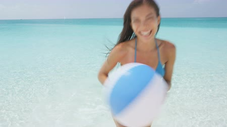 sensuous : Excited young woman holding beach ball coming out of sea. Portrait of cheerful woman in bikini running in water. Sensuous female is enjoying her summer vacation on beach