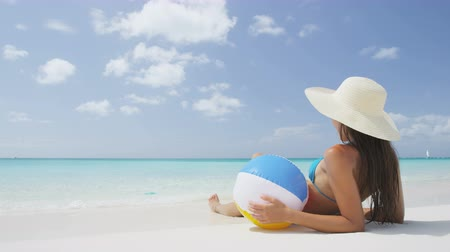 sensuous : Relaxing young beach woman lying sown in perfect white sand holding ball. Female is wearing blue bikini and sunhat while sunbathing. Girl is at beach during summer vacation travel getaway trip. Stock Footage