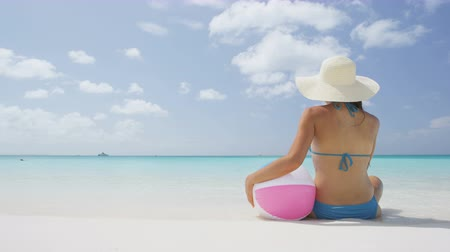 сидеть : Beach travel vacation holidays concept. Woman woman holding beach ball sitting on sea shore. Rear view of female wearing blue bikini and sunhat while sunbathing. Young woman is relaxing on beach.