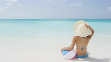 sensuous : Sensuous young woman holding ball while sitting on sea shore. Rear view of female wearing blue bikini and sunhat while sunbathing. Young woman is relaxing on idyllic beach during summer vacation.
