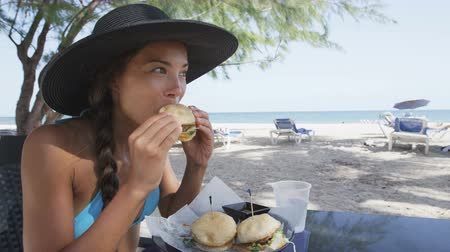 sandviç : Beautiful young woman eating sandwich at beach restaurant. Young female is enjoying snacks sitting at table. Beautiful tourist in bikini and sunhat is on her summer vacation on Dover Beach, Barbados. Stok Video