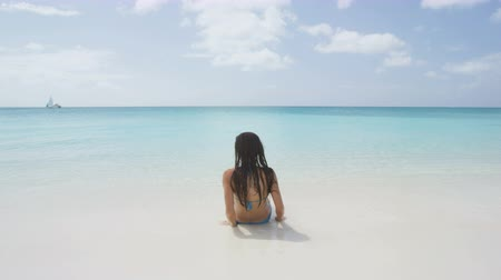 sensuous : Beautiful young woman coming out of sea during summer. Smiling female in blue bikini is walking towards shore. Sensuous woman is relaxing on beach during her vacation. Stock Footage