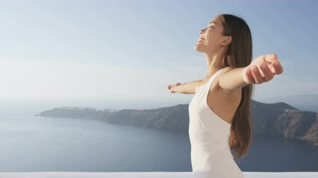 наслаждаться : Serenity free carefree young woman standing with arms outstretched relaxing in enjoying freedom. Happy girl on Santorini, Greece. Attractive lady in white sundress on summer vacation travel