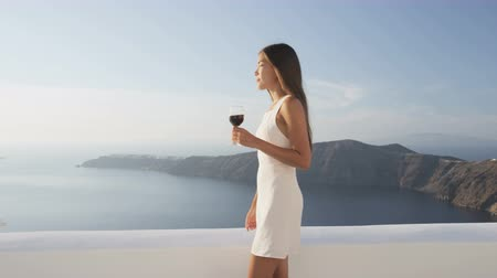estilo de vida : Woman holding red wine glass while drinking and walking by nature enjoying luxury lifestyle. Elegant model in white sundress on summer vacation on Santorini, Greece.