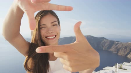çerçeveler : Cheerful young woman making frame with hands. Portrait of female winking while looking through imaginary camera made with fingers. Attractive lady on Santorini, Greece during summer holidyas.