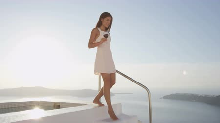 holiday villa : Elegant woman in luxury villa outdoors drinking red wine. Smiling young woman holding wine glass walking by swimming pool. Female in white sundress enjoying beautiful view of nature, Santorini. Greece Stock Footage
