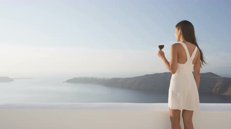 erkély : Young woman with glass of red wine walking on terrace. Asian female is looking at view of sea on balcony wearing white sundress during vacation travel on Santorini, Greece. RED EPIC SLOW MOTION. Stock mozgókép