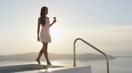 джакузи : Luxury travel lifestyle woman with glass of red wine walking at the edge of swimming pool. Female is enjoying her drink by sea during sunset. Female model on vacation holidays on Santorini, Greece.