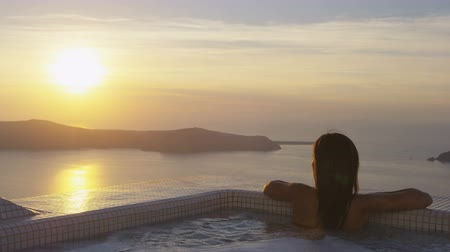 джакузи : Asian woman relaxing at the edge of swimming pool at resort. Young female is watching beautiful view of sunset. She is enjoying her vacation at resort by sea. Santorini, Greece.