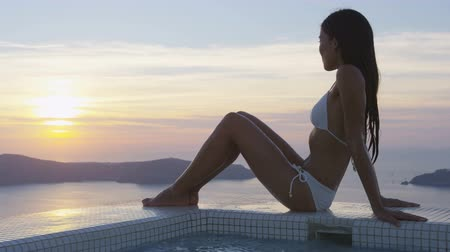 bordas : Sexy beautiful woman in bikini sitting at the edge of swimming pool. Young female is watching beautiful view of sunset. She is enjoying her vacation at resort by sea. Santorini, Greece. Stock Footage