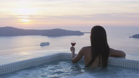 джакузи : Jet set Travel woman in bikini in pool by amazing sunset view. Model placing glass of red wine at the edge of swimming pool. Asian female is enjoying her vacation on Santorini, Greece. RED EPIC.