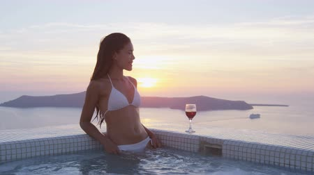 джакузи : Happy young woman wearing bikini while relaxing in swimming pool. Glass of red wine is kept at the edge of pool. She is enjoying her vacation at resort by sea during sunset. Santorini, Greece.