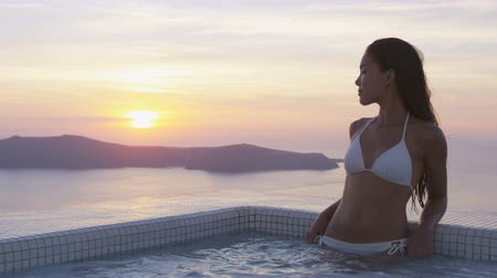 estância turística : Sensuous woman in bikini looking at sunset over sea. Young Asian female in resting in swimming pool. She is enjoying her vacation at resort. Santorini, Greece.