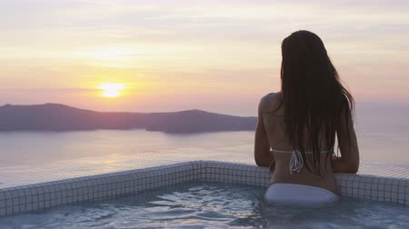 джакузи : Young woman relaxing in swimming pool. Asian female is in bikini watching beautiful view of sunset. She is enjoying her vacation at resort by sea. Santorini, Greece. Стоковые видеозаписи