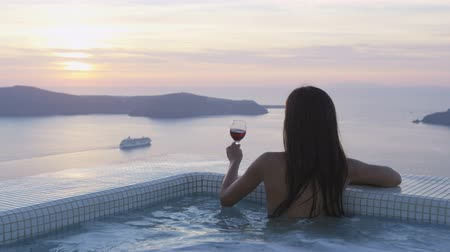 джакузи : Luxury travel lifestyle woman in pool at sunset. Young woman having glass of red wine in swimming pool. Asian female is watching sunset over sea. She is enjoying her vacation on Santorini, Greece.